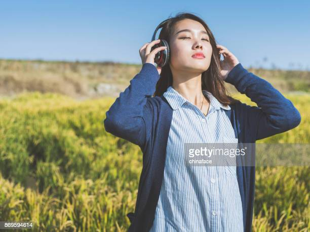 young girl wearing headphones in field