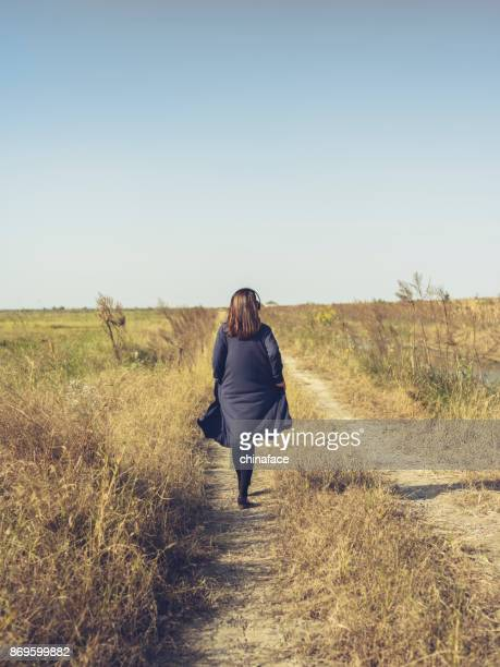 young girl wearing headphones walking on dirt road