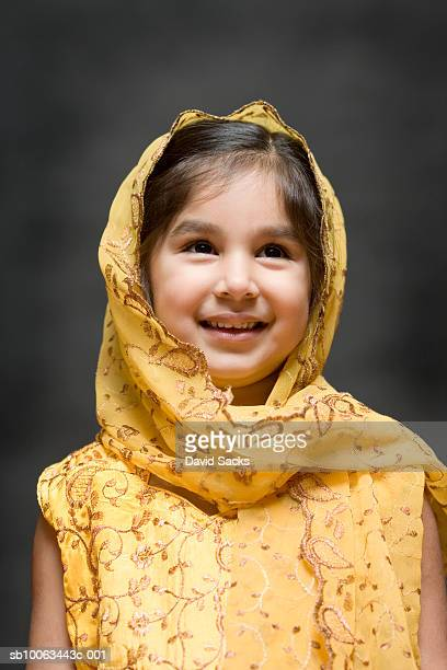 Young girl (4-5) wearing headscarf, smiling