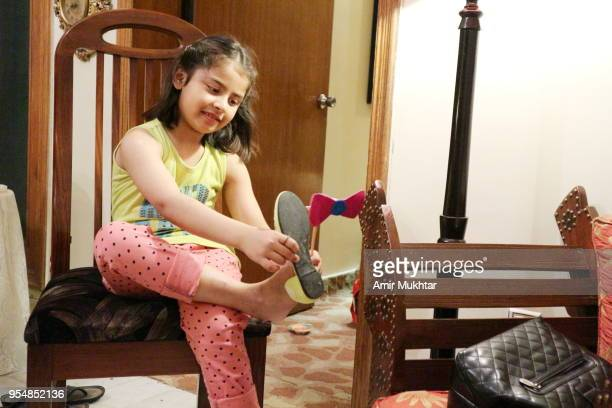 A young girl wearing her shoe in a birthday party