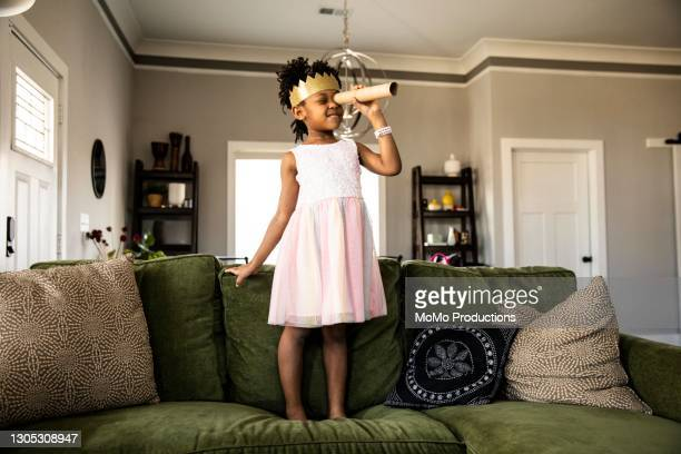 young girl wearing homemade crown and looking through homemade telescope - royalty stock pictures, royalty-free photos & images