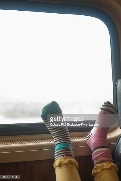 Young girl wearing mismatched socks with her feet up on train compartment window