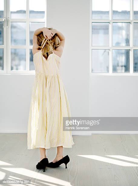 young girl (6-7) wearing mother's dress and shoes, rear view - tacchi alti foto e immagini stock