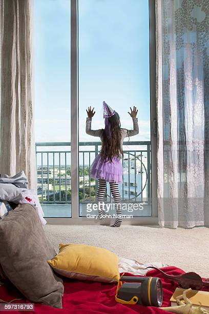 Young girl, wearing party clothes, looking out of window, rear view