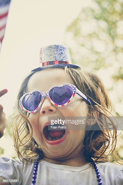 Young girl wearing patriotic hat and sunglasses