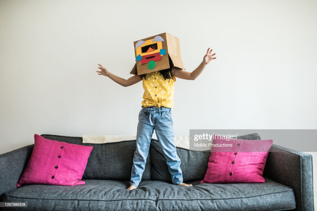 Young girl wearing robot costume at home : Stock Photo
