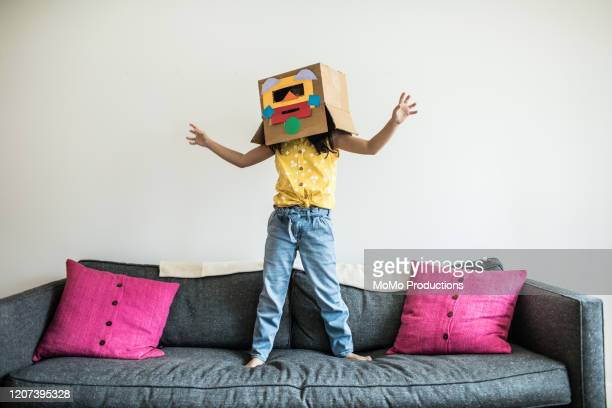 young girl wearing robot costume at home - playing stock-fotos und bilder
