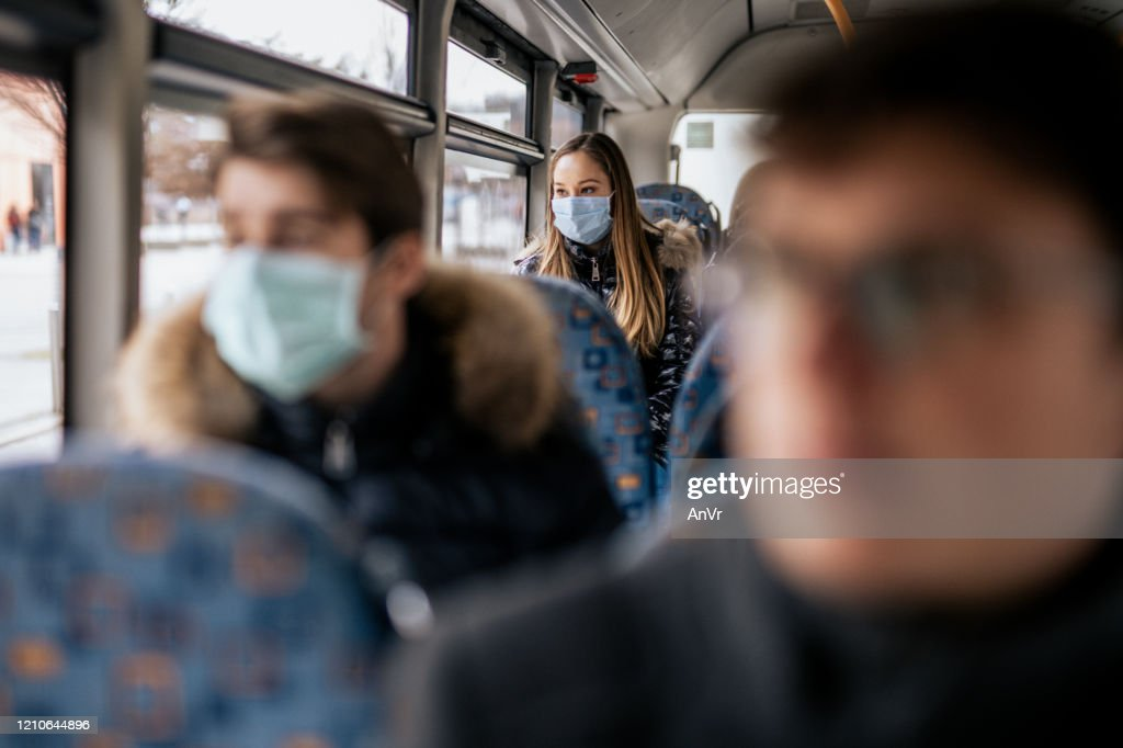 Young girl wearing sterile face mask using a public transport : Stock Photo