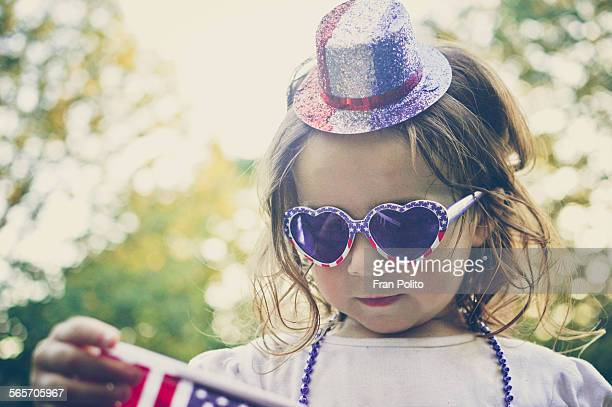 Young girl wearing sunglasses holding the USA flag