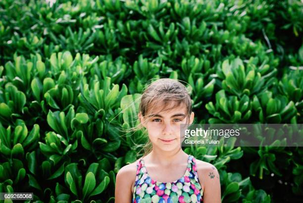 Young girl wearing swimsuit on green leaf background on the beach.