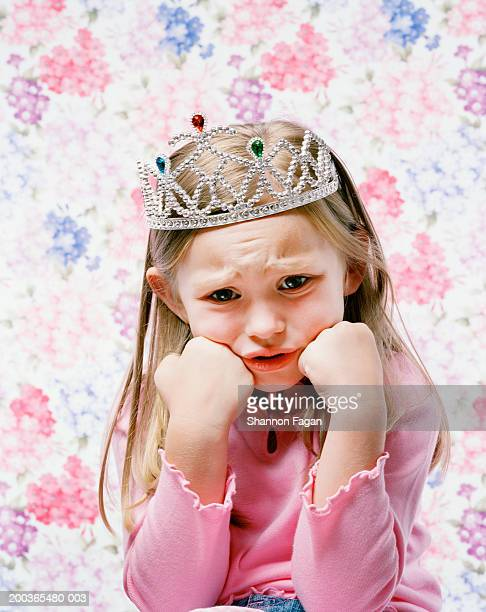 Young girl (4-6) wearing tiara with sad face, portrait
