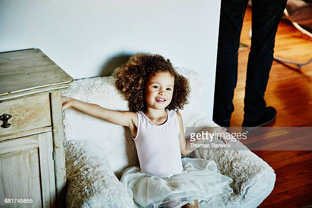 Young girl wearing tutu sitting in chair