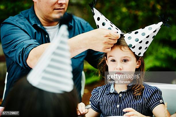 Young girl wearing two party hats