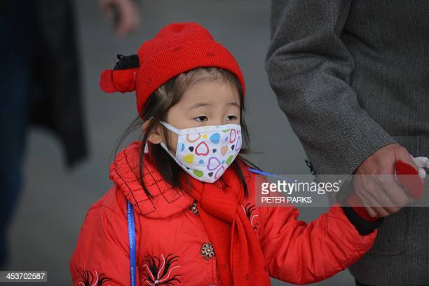 A young girl wears a face mask on a street in downtown Shanghai as severe pollution hits the city on December 5 2013 Authorities issued warnings for...