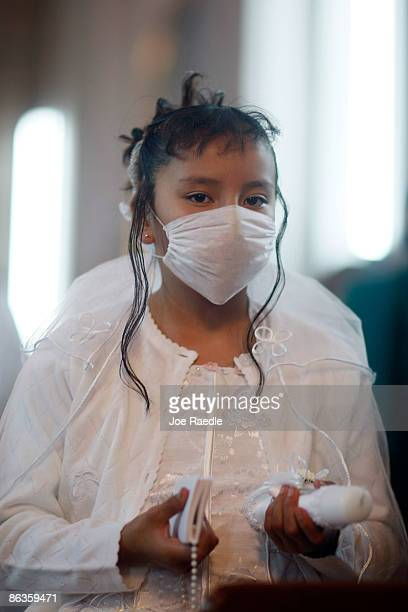 A young girl wears a surgical mask to help prevent catching the swine flu during a church service on May 3 2009 in Mexico City Mexico The Mexican...