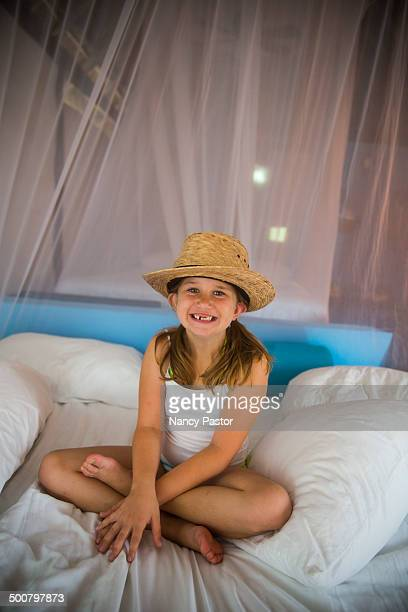 A young girl wears straw hat.
