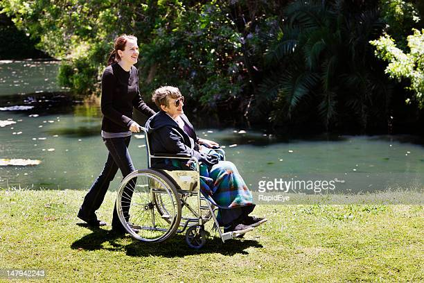 Young girl wheels old woman in wheelchair by lake