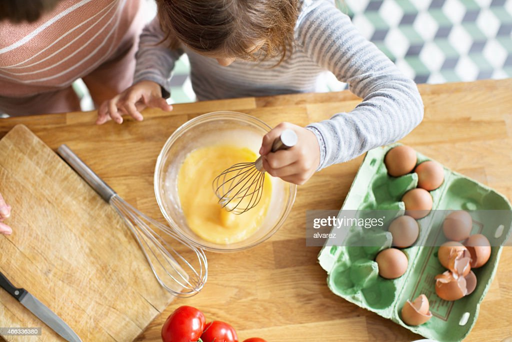 Young girl whipping eggs in a bow : Stock Photo
