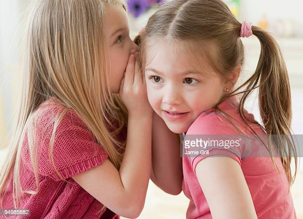 Young girl whispering a secret to another girl
