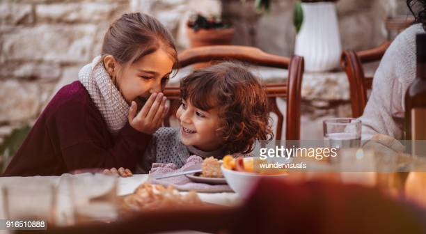 young girl whispering secret in boy's ear at family lunch - spain italy stock pictures, royalty-free photos & images