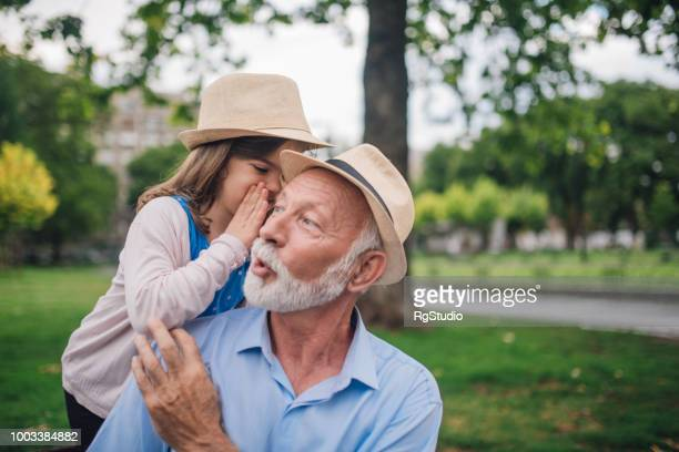 Young girl whispering secrets to her grandpa