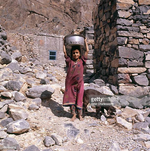 A young girl who lives in a small village of stone houses in the Al Hajar Mountains carries a bowl on her head as a goat looks for food