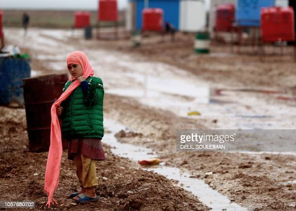 A young girl who was displaced with families from Deir Ezzor and its surroundings walks in the mud at a camp for displaced people near the town of...