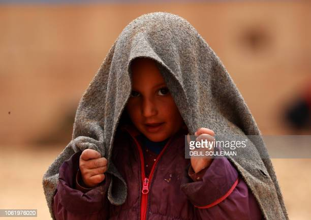 A young girl who was displaced with families from Deir Ezzor and its surroundings stands covering herself with a blanket outside at a camp for...