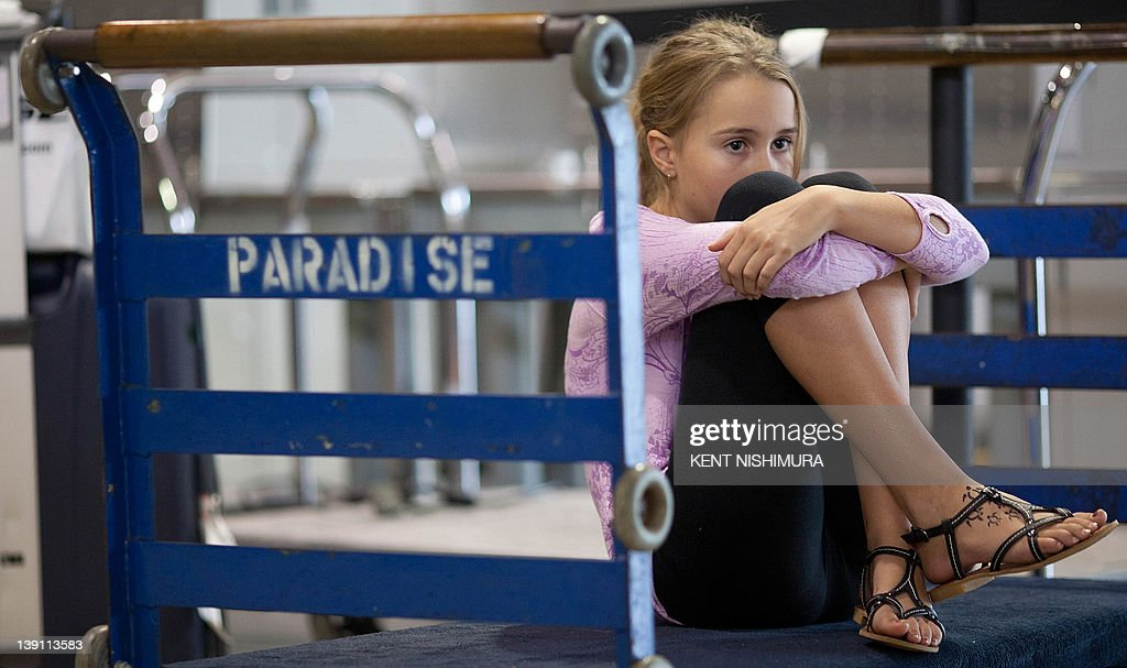 A young girl who would not give her name sits on a luggage trolley near the Air Australia ticket counter at Honolulu International Airport on Thursday, February 16 , 2012 in Honolulu, Hawaii. Budget carrier Air Australia went into voluntary administration, grounding all domestic and international flights and stranding thousands of passengers. AFP PHOTO / Kent NISHIMURA