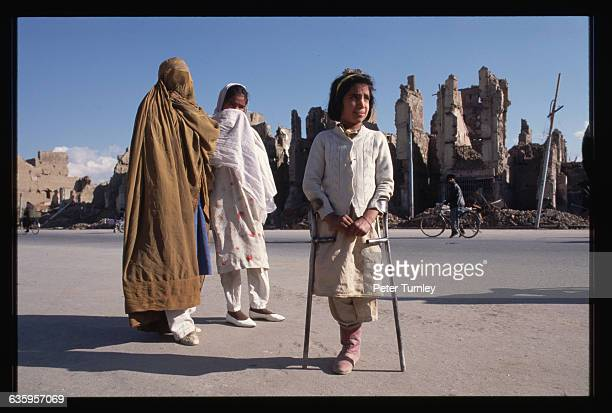 A young girl whose leg had to be amputated because of a land mine accident stands on crutches with two other Afghanistani girls Behind are bombedout...