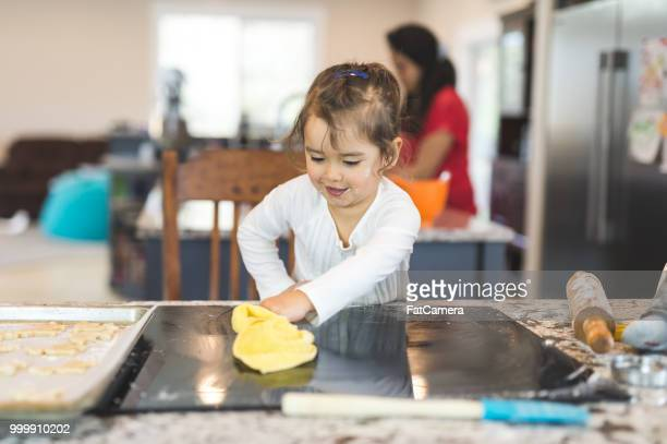 Young girl wipes the counter down after baking cookies