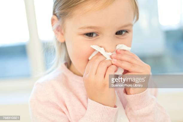 Young girl wiping nose on tissue