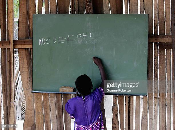 A young girl wirtes the alphabet on a blackboard in her school on June 30 2005 in Mozambique Since Mozambique's 15year civil war ended in 1992 the...