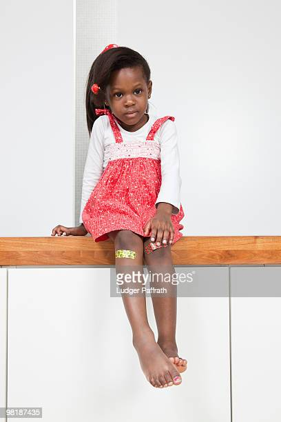 A young girl with a bandage on each knee