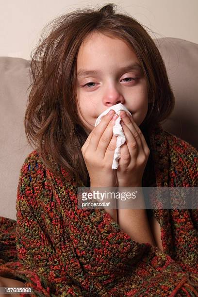 young girl with a cold blowing her nose  - clown's nose stock photos and pictures