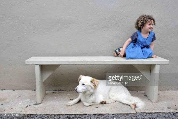 Young girl with a dog sitting on a bench