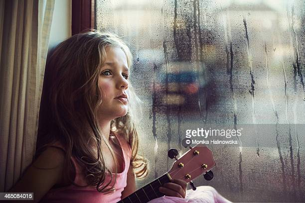 Young girl with a guitar beside a window