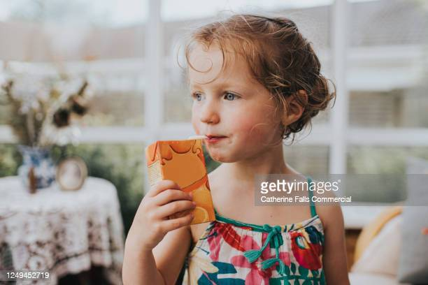 young girl with a juice box, sucking on a straw - innocence stock pictures, royalty-free photos & images