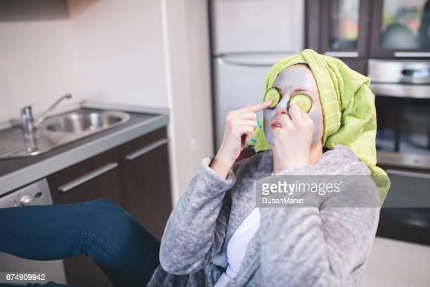 junges Mädchen mit einer Maske für Haut Gesicht und Gurken auf den Augen