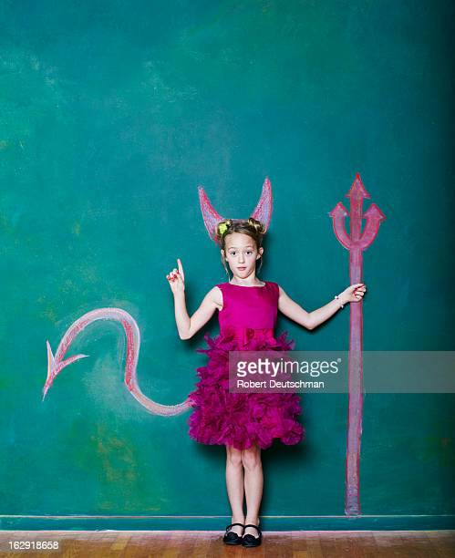 a young girl with a pitchfork and horns. - devil costume stockfoto's en -beelden