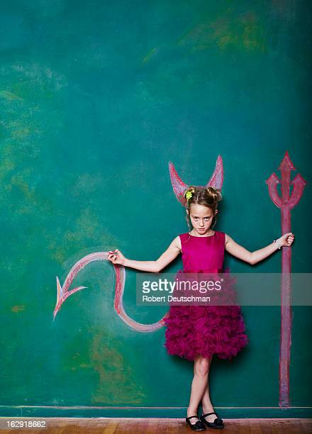 A young girl with a pitchfork and horns.
