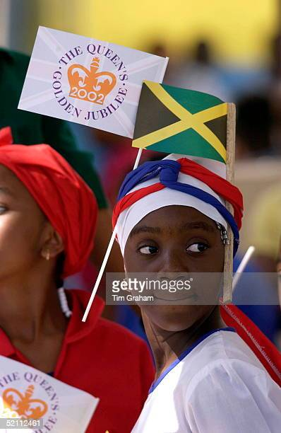Young Girl With A Queen's Jubilee Flat And The Jamaican National Flag Slotted Through Her Headband She Is Waiting In Sam Sharpe Square For The Queen...