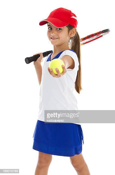 A young girl with a tennis racket holding out a tennis ball
