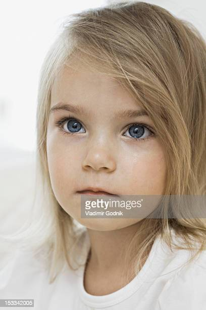 A young girl with a wet cheek from crying