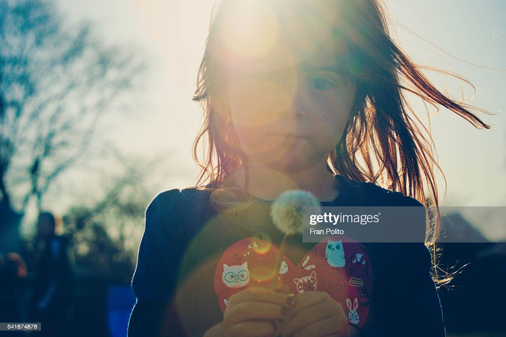 Young girl with a wish flower. : Stock Photo