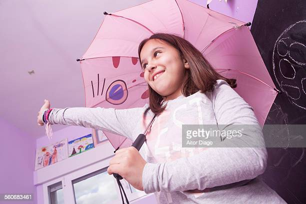 Young girl with an umbrella in her room.