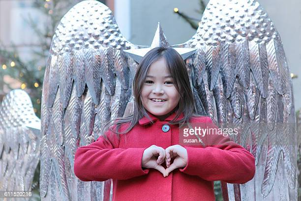 Young girl with angel wings making heart shape with hands