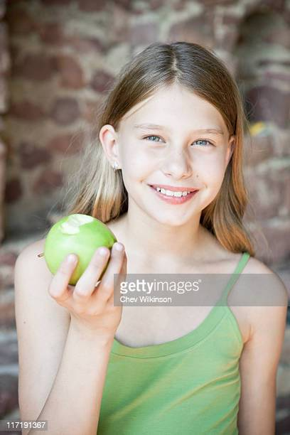 young girl with apple - kid girl eating apple stock photos and pictures