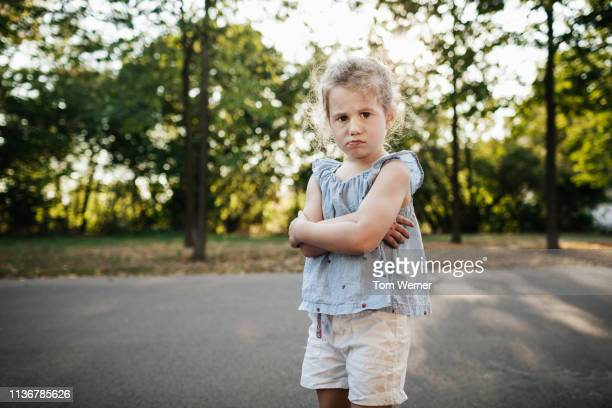 young girl with arms folder at the park - sulking stock pictures, royalty-free photos & images