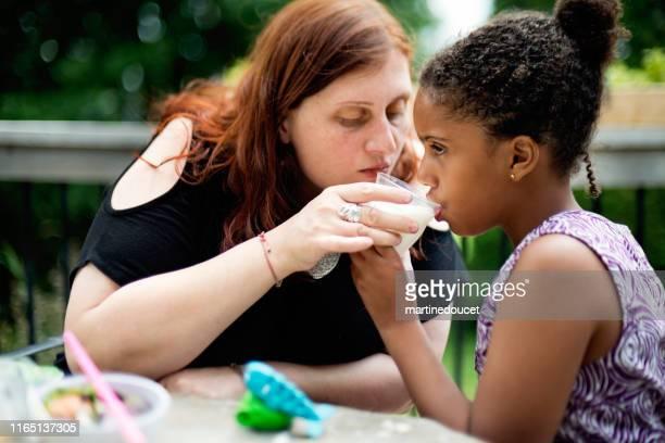 """junges mädchen mit autismus trinken milch mit hilfe der mutter im freien. - """"martine doucet"""" or martinedoucet stock-fotos und bilder"""